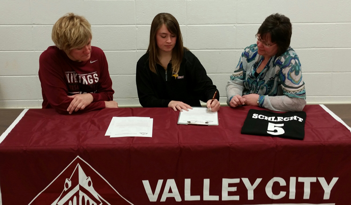 Hannah Schlecht signs her letter of intent to play basketball at Valley City State University.