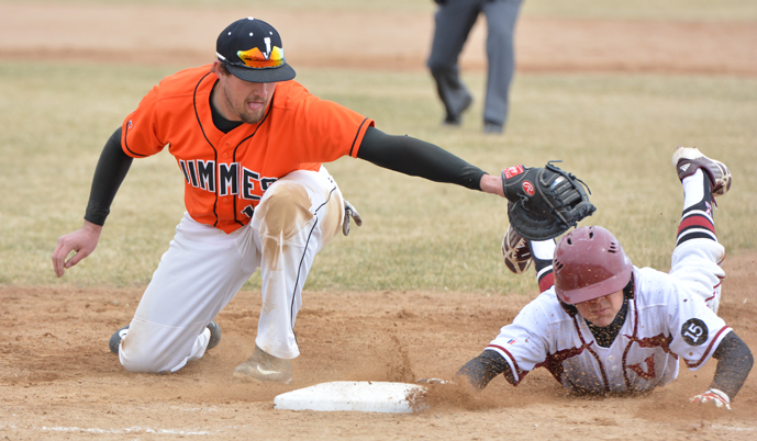 VCSU's Xavier Padilla dives back to first base, just ahead of the tag by Jamestown's Tyler Wiwchar. (Mark Potts/VCSU)