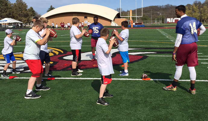 Participants in the Youth Football Camp learn QB fundamentals from VCSU quarterbacks Kurtis Walls (14) and Justan Taliaferro.